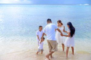 Familie tanzt im seichten Meerwasser